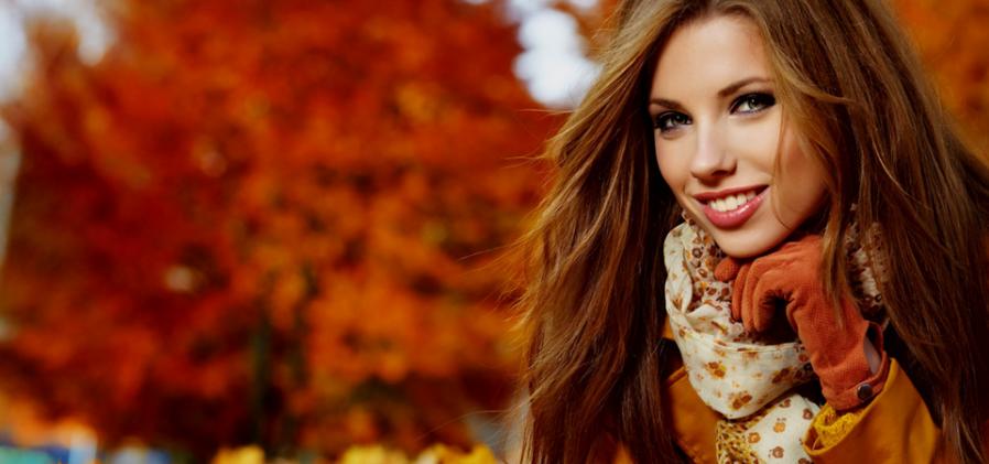Vrouw met lang bruin-rood haar ligt in herfstbladeren