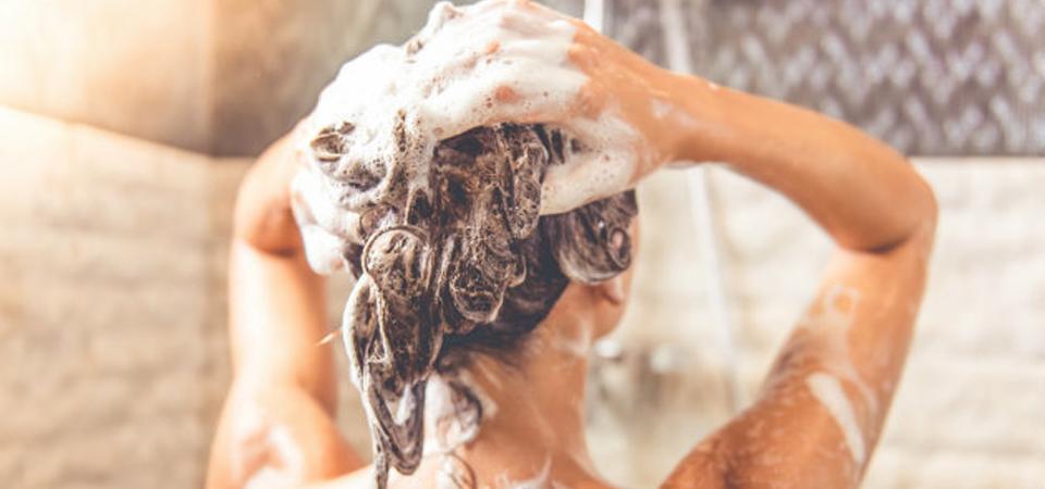 Vrouw wast haar onder de douche